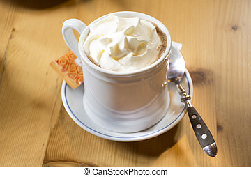 White cup with hot chocolate topping whipped cream serve with sugar bag in restaurant at Samnaun village in Graubunden, Switzerland
