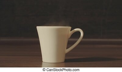White cup with hot drink on the table. Close up 4K
