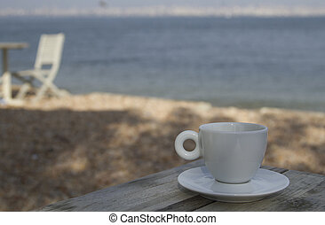 White cup with saucer on the wooden table near sea