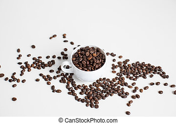 white cup with scattered coffee beans, isolated on white