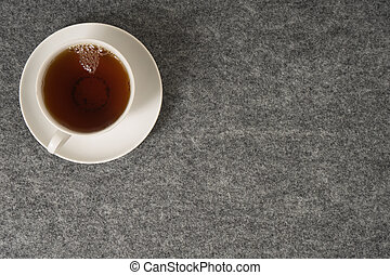 White cup with tea on a black background. Top view.