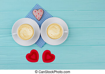 White cups with cappuccino and red hearts.