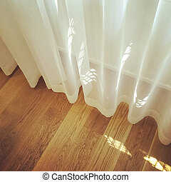 White curtain in a room with wooden floor