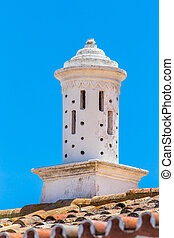 White decorative chimney on roof with blue sky