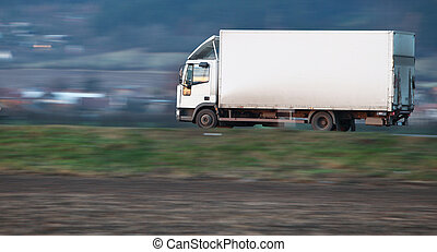 white delivery truck going fast on a road (panned image - motion blur is used to convey movement; the truck is reasonably sharp while the surrounding landscape is blurred)