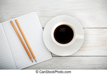 white desk with cup of coffee, pencil; notebook. lay flat