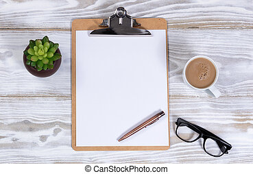 White desktop with blank clipboard and paper plus coffee