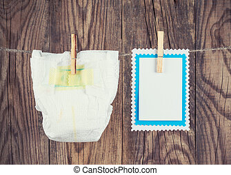 white diaper and blank note hanging on clothesline against woode