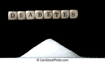 White dice spelling diabetes falling over a pile of sugar on...