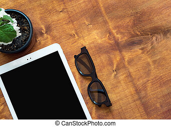 White digital tablet with black glasses and green flower on wood table, top view