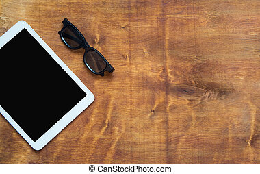 White digital tablet with black screen and black glasses on wood table. Copy space