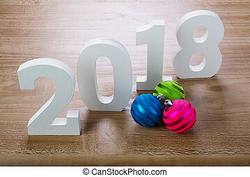 White digits 2018 with Christmas balls on wooden background