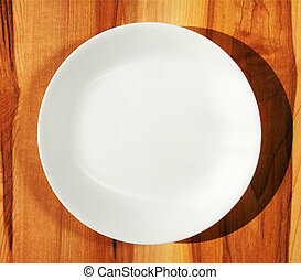 White dinner plate on wood table - Pure white porcelain...