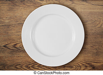 white dinner plate on wooden table top view