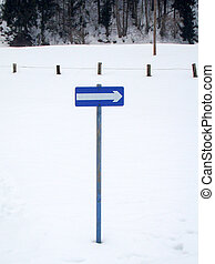 white direction arrow on blue sign in the snow