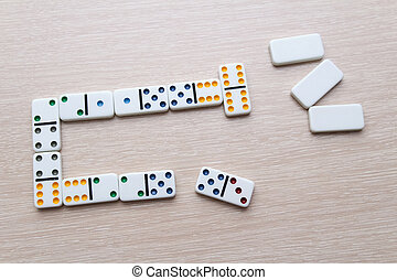 white Domino dice on a light wooden table, the process of playing dominoes