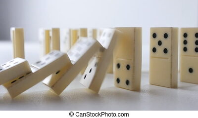 White Dominoes Falling in Chain Reaction
