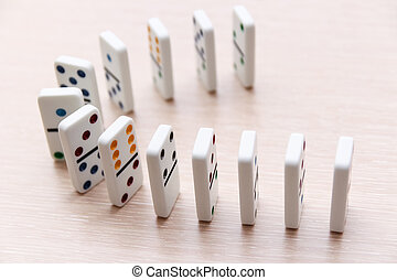 white dominoes stand in a row on a light surface, close-up