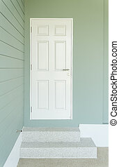 white door on the blue wall and two steps leading to entrance