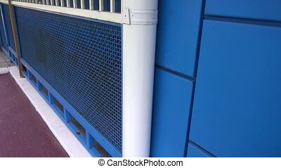 white downpipe on the background of blue wall