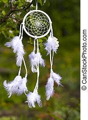 White Dreamcatcher against the background of a green garden