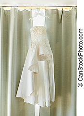 White dress of the bride of the original design on a hanger with a bow tie of the groom against the background of curtains.