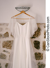 White dress of the bride on a wooden hanger against a stone wall with a sconce.