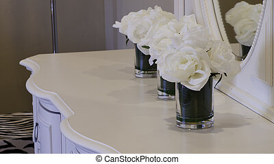 White dresser with white flowers.
