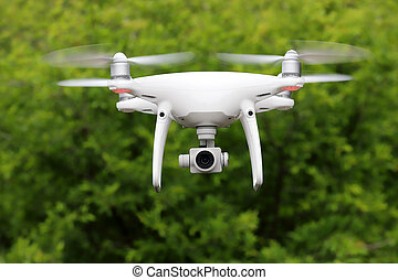 White drone flying in the forest