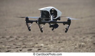 White drone flying on agricultural field background, drone...