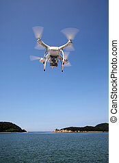 White drone quad copter with flying in the clear blue sky