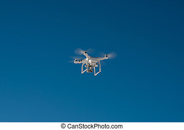 White drone quad copter with flying in the blue sky