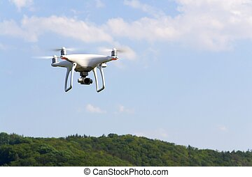 White drone quadrocopter with camera flying over forest