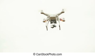 White drone, quadrocopter, with photo camera flying in the blue sky