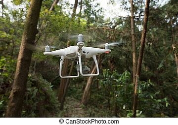 White drone with camera flying over forest