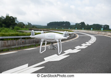 White drone with camera flying over highway