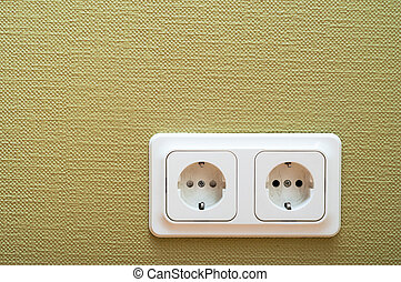 White dual socket on green wall