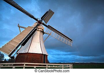 white Dutch windmill in sunset light