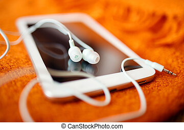 White earphones and tablet pc, close up photo, small dof