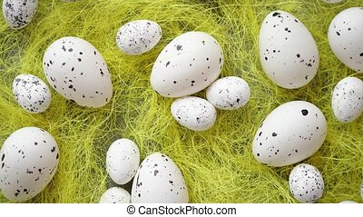 White Easter eggs with freckles placed on the yellow hay....