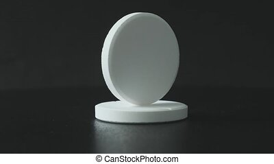 White effervescent tablets on black background
