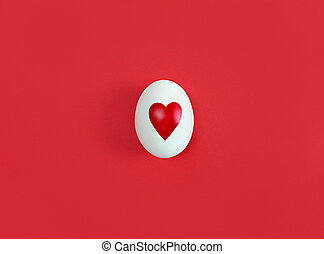 White egg with heart shape on red background.