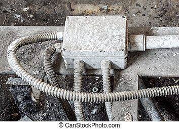 White electric box with three black cables on the old red brick wall.