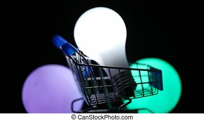 white electric lamp in toy shopping trolley rotating, color lights on background