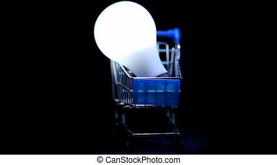 white electric lamp in toy shopping trolley rotating on black