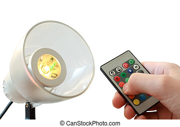 White electrical lamp, near it remote controller in man hand
