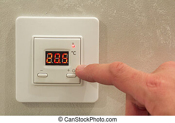 White electronic programmable digital thermostat on light wall copy space background. Climate control, comfortable home temperature, energy saving concept.