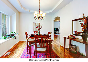Beautiful coffered ceiling dining room with a hardwood floor. Furnished with a served dining table set.