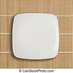 white empty bowl on a bamboo table