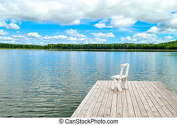 White empty deck chair at the lake dock.